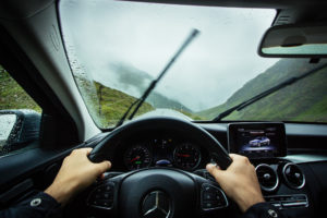 Windshield wipers wiping a wet windshield while hands grip the wheel